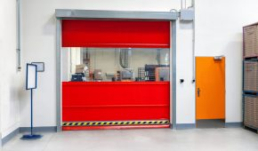 Horizontal color image of industrial red door in large factory.