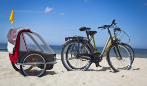 Summer scene with  bicycles and a baby trailer on the sandSee more ON THE BEACH images here: