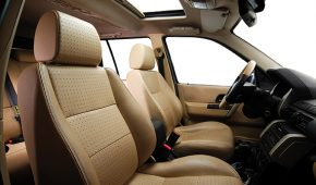 beige colored leather car seats, seatbelts, dashboard of the car from side view